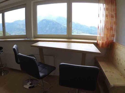 Essbereich mit Bank, Tisch, Stühle, Hocker, im Hintergrund Panoramaausblick durch die Fenster auf die Berge. (© Wiener)