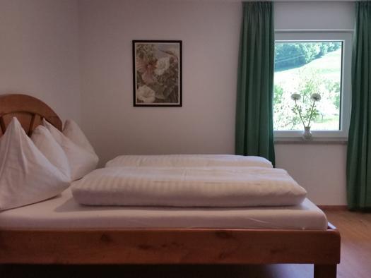 Doppelbett, im Hintergrund ein Fenster, Bild an der Wand. (© Tourismusverband MondSeeLand)