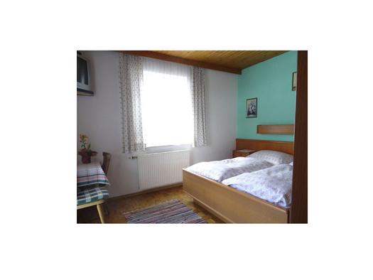 Schlafzimmer mit Doppelbett, im Hintergrund ein Fenster, seitlich Tisch mit Stuhl. (© Feusthuber)