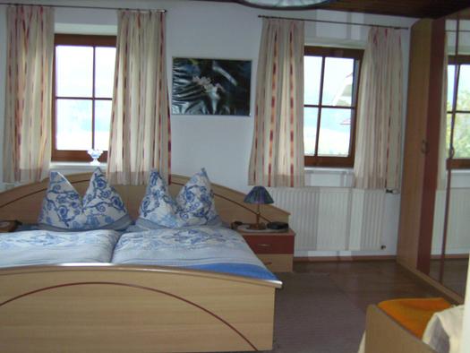 Schlafzimmer mit Doppelbett, Nachtkästchen, Tischlampen, im Hintergrund Fenster, seitlich ein Kleiderschrank mit Spiegel. (© Niederbrucker)