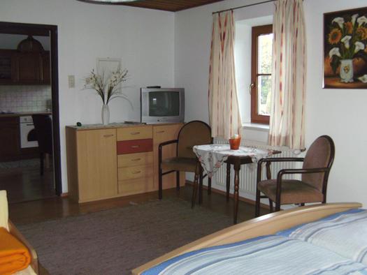 Schlafzimmer mit Doppelbett, im Hintergrund Kommode mit Fernseher, Blumenvase, seitlich Tisch und Stühle, Fenster, Blick durch die offene Tür im Hintergrund in die Küche. (© Niederbrucker)