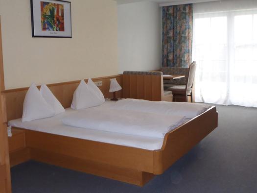 Schlafzimmer mit Doppelbett, im Vordergrund ein Teil vom Stockbett - seitlich, im Hintergrund Sitzgelegenheit mit Sessel, Bank und Tisch. (© Szarzinsky)