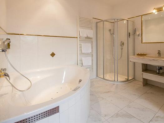 Blick ins Badezimmer mit rechts einer Eckbadewanne, im Hintergrund Dusche und rechts das Waschbecken mit großem Spiegel. (© Karin Lohberger)
