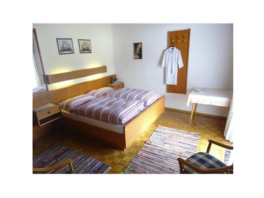 Schlafzimmer mit Doppelbett, Nachtkästchen, Garderobe an der Wand, Tisch. (© Feusthuber)