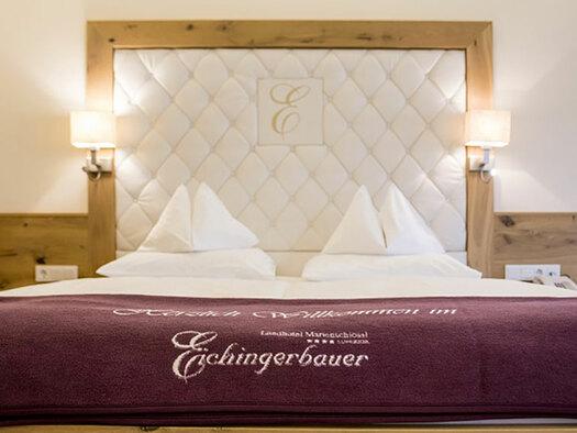 Doppelbett mit Tagesdecke und Beleuchtung. (© Karin Lohberger)