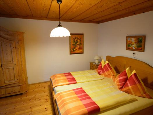 Schlafzimmer mit Doppelbett, Kleiderschrank seitlich hinten im Bild, Holzboden. (© Mairhofer)