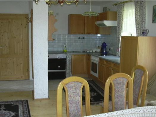 Wohnbereich, im Hintergrund Küche mit Herd, Spüle, Herd, Kaffeemaschine, Fenster, im Vordergrund Stühle. (© Handl)