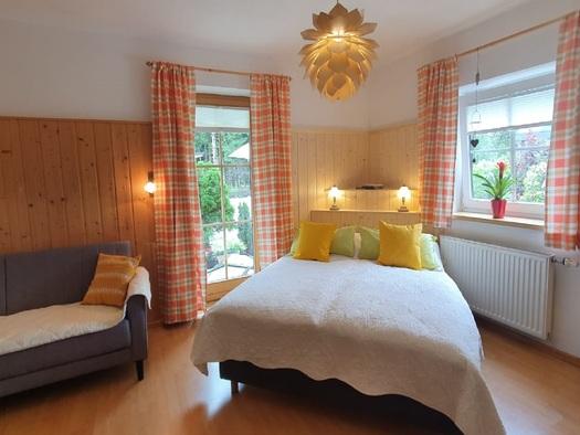 Helles, liebevoll eingerichtetes Schlafzimmer mit bequemen Boxspringbett und Schlafcouch. (© Gabriele Untersberger)
