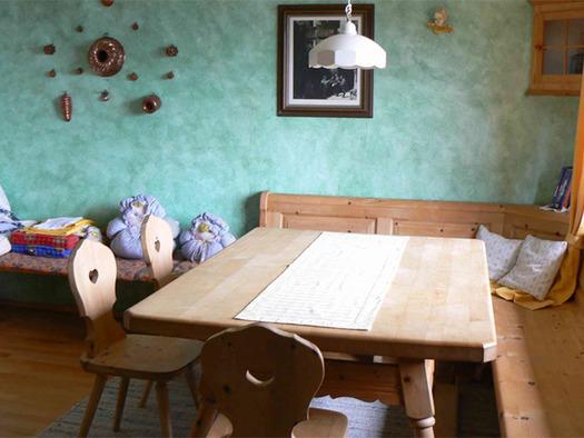 Eckbank mit Tisch und Stühle, Bild an der Wand. (© Riess)