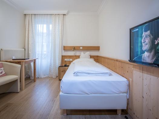 Zimmer mit Einzelbett Flachbild TV an der Wand und Tisch mit Sessel. (© Familie Ragginger/Klaus Costadedoi)