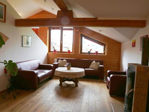 Blick in den Wohnbereich mit Couch, Tisch, Holzboden, im Hintergrund Fenster. (© Familie Radauer)