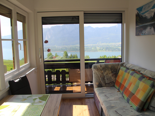 couch, table, french window, view at the lake. (© Tourismusverband MondSeeLand)