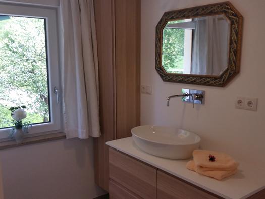 Waschbecken, Spiegel, seitlich ein Fenster. (© Tourismusverband MondSeeLand)