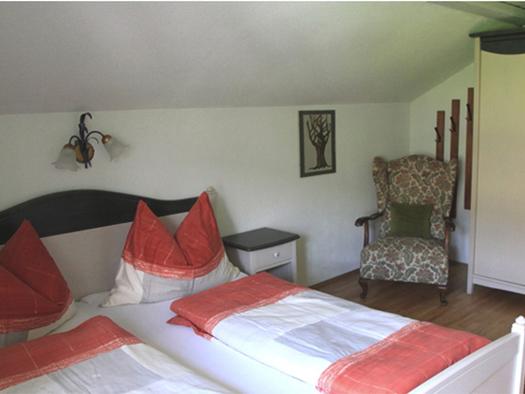 Schlafzimmer mit Doppelbett, Nachtkästchen, gemütlicher Sessel, Kleiderschrank. (© Edtmayer)