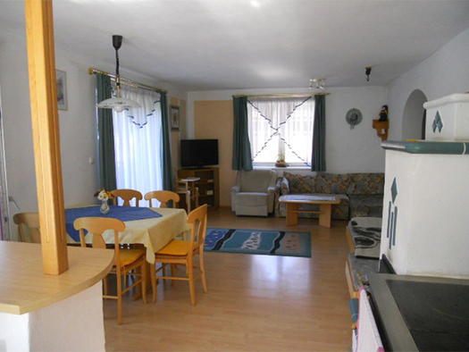 Wohnbereich, seitlich Tisch mit Stühle, Balkontür, im Hintergrund Fernseher, Fenster, Sessel, Couch, kleiner Tisch, Kachelofen. (© Handl)