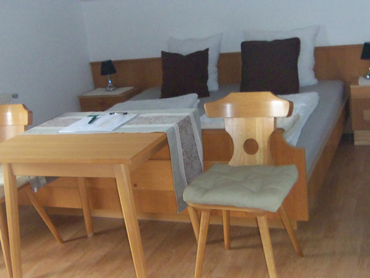 Schlafzimmer mit Doppelbett, davor ein Tisch mit Stühlen. (© Schafleitner-Kroiß)