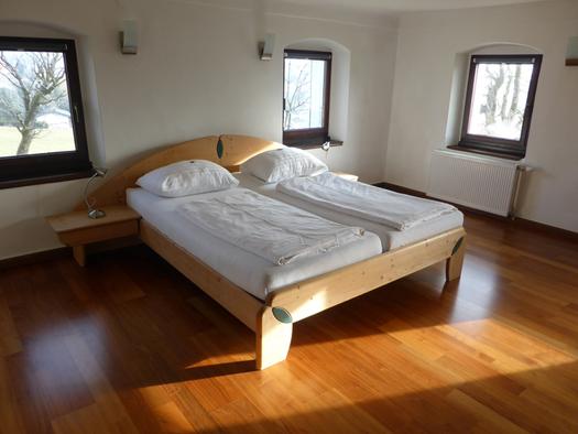 Doppelbett, im Hintergrund und seitlich Fenster. (© Taubenberger)
