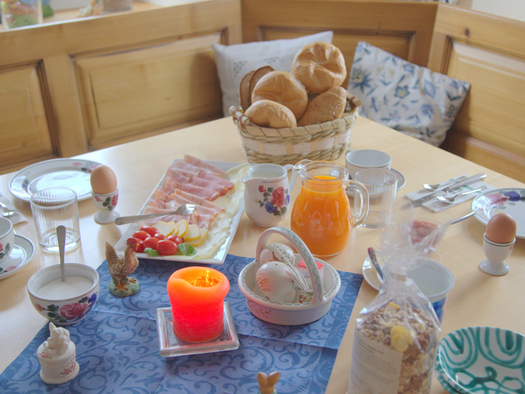 Breakfast table with rolls, eggs, ham, cheese,. coffee and orange juice.