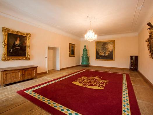 Prunkraum mit große Gemälde an der Wand, alte Kommode, großer Teppich. (© Schloss Mondsee)