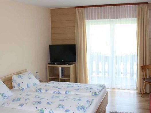 Zimmer mit Doppelbett im Hintergrund ein Fernseher und eine Balkontür. (© Marx zu Mayerhof)