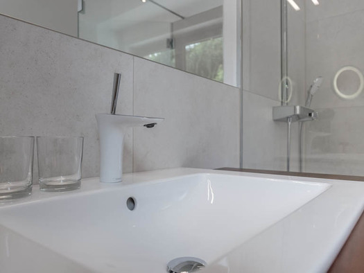 Sink, glasses, mirror, in the background the shower. (© Lackner)