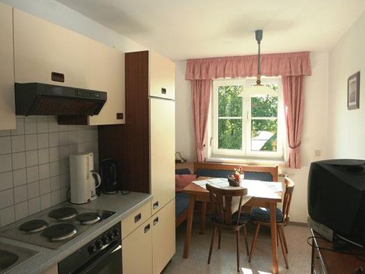 Blick in die Küche mit Herd, Herdplatten, Kaffeemaschine, im Hintergrund ein Essplatz mit Bank, Tisch und Stühle, Fenster. (© Maier)