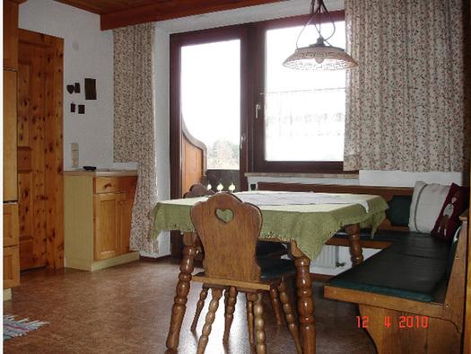 Essbereich mit Eckbank, Tisch und Stühle, im Hintergrund Balkontür und Fenster. (© Familie Laireiter)