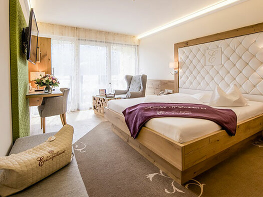 Right the Bed, in the Background a fauteuil and the doors to the balcony, on the left Hand side a flatscreen. (© Karin Lohberger)