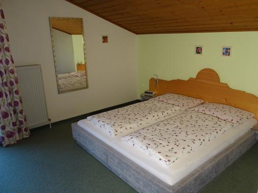 Doppelbett, seitlich ein Spiegel an der Wand. (© Pichler)