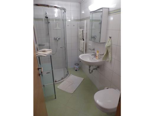 Badezimmer mit rechts die Toilette, dann das Waschbecken mit Spiegelschrank, im Hintergrund der Handtuchhalter und links die Duschkabine. (© Mayrhofer)