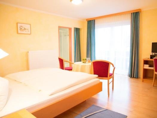 Doppelzimmer mit großem Doppelbett, Sitzgelegenheit, Schreibtisch, SKY-TV und Balkon. (© Ertl)
