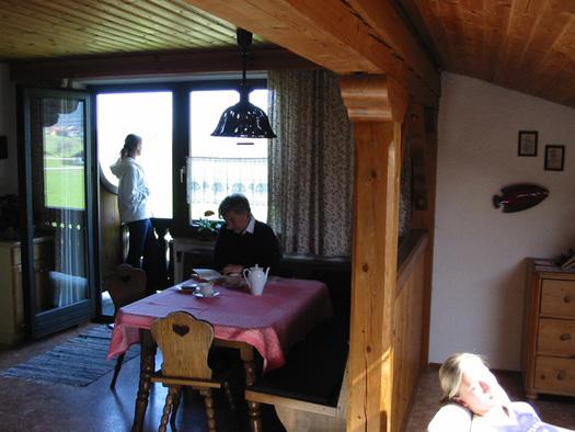 Wohnbereich, Person sitzt auf der Eckbank bei gedecktem Tisch und liest ein Buch, Blick durch die Balkontür, Person steht am Balkon, seitlich sitzt eine Person. (© Familie Laireiter)