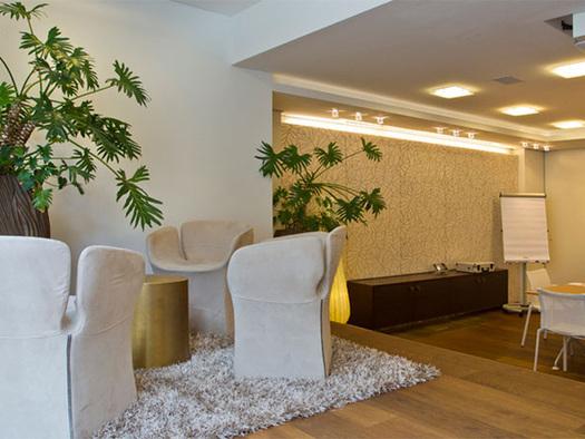 Seminarraum mit Tischen und Stühlen, Beamer an der Decke, Pflanzen. (© Hotel Iris Porsche)