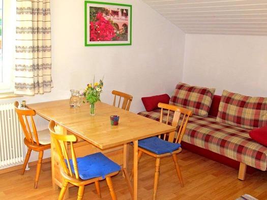 Wohnbereich in der Ferienwohnung Drachenwand mit Sitzgelegenheit, Tisch und Stühle, im Hintergrund eine Couch. (© Gästehaus Horizont)