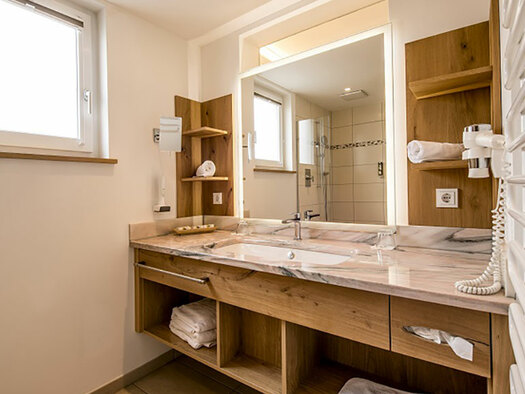 View to the bathroom with wooden furniture and lavatory and mirror. (© Karin Lohberger)