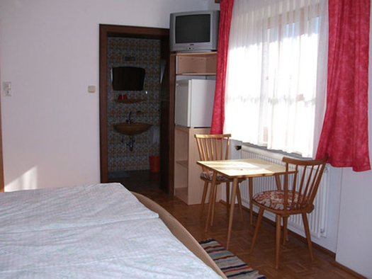 Bedroom with doublebed, table, chairs, TV and a big window. In the background the bathroom is visible. (© Schwaighofer)