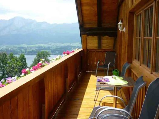look at the balcony with chairs and a table, lake and mountains in the background. (© Edtmeier)