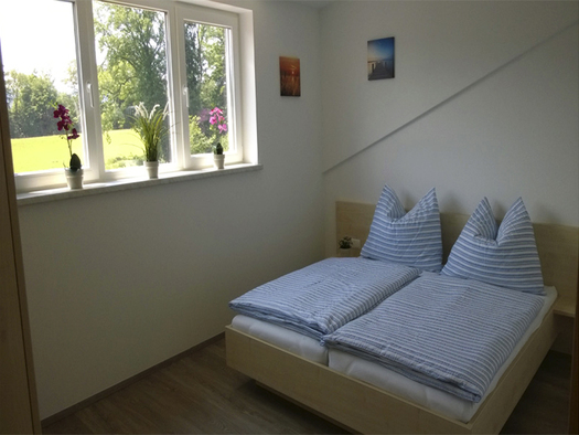 Bedroom with double bed, on the side a window with garden view. (© Wienerroither)