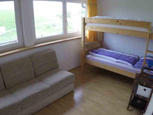 Schlafzimmer mit Stockbett, seitlich eine Couch, Fenster. (© Wiener)