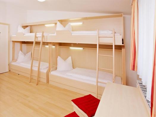 Schlafzimmer mit einzelnen Stockbetten mit Leiter, seitlich ein länglicher Tisch mit Hocker. (© Jugendhästehaus)