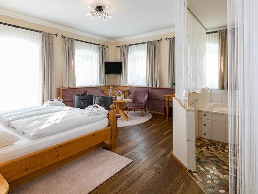 Blick auf das Badezimmer, Doppelbett mit 2 grauen Taschen vorne, Schreibtisch an der Wand mit Stuhl, kleiner Tisch mit Blumen und Flasche, zwei Sessel, Fernseher an der Wand. (© Eichingerbauer)