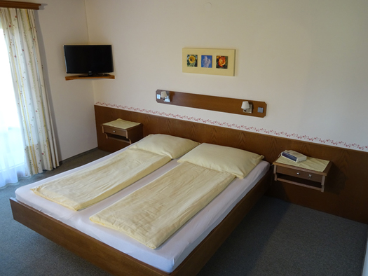 Doppelbett, Nachtkästchen, seitlich eine Balkontür. (© Pichler)
