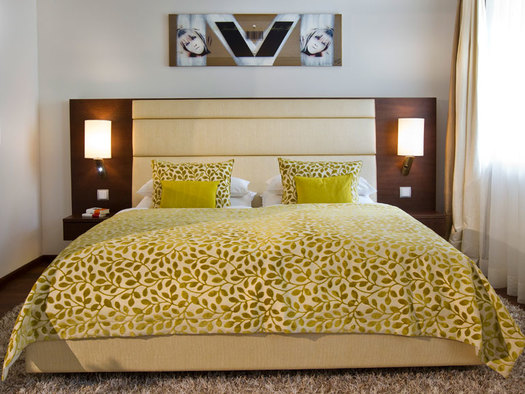 Bed with Pillows and lamp on side. (© Iris Porsche Hotel)