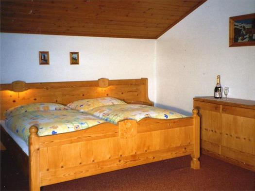 Schlafzimmer mit Doppelbett, seitlich eine Kommode mit einer Flasche und Gläser. (© Pichler)