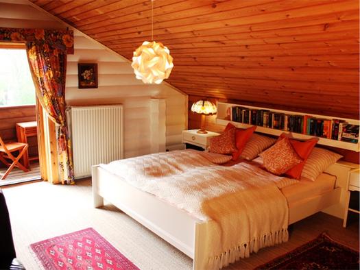 Schlafzimmer mit Doppelbett, Nachtkästchen, im Hintergrund Blick durch die offene Balkontür. (© Schorn)