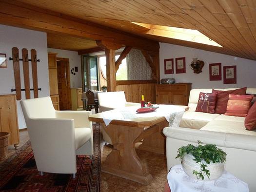 Wohnbereich mit Couch, Polster, Tisch und Stühle, im Vordergrund ein kleiner Tisch mit einer Pflanze, im Hintergrund Blick in den Essbereich, Balkontür und Fenster. (© Familie Laireiter)