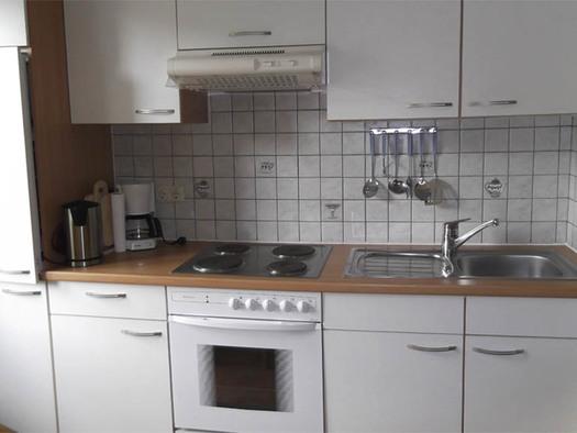 Küche mit Ofen, Abwasch, Kaffeemaschine, Wasserkocher, verschiedene Küchenutensilien hängen an den Fliesen. (© Knoblechner)
