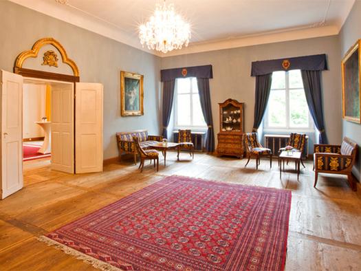 Holzboden, Teppich, Tische und Stühle, Sofa, große Fenster im Hintergrund und eine alte Vitrine. (© Schloss Mondsee)