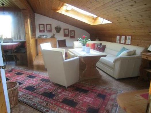 Wohnbereich mit Couch, Tisch, Sesseln, Kommode im Hintergrund, seitlich im Hintergrund Essbereich mit Eckbank, Tisch, Fenster. (© Familie Laireiter)