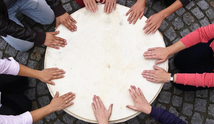 viele Hände auf einem Tisch